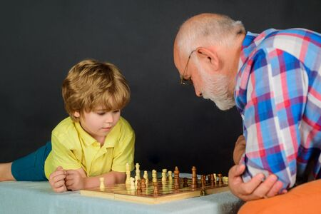 Child boy playing chess with grandfather. Games and activities for children. Checkmate. Little boy think or plan chess game. Grandfather and grandson playing chess. Little boy learning to play chess