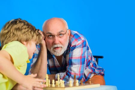 Child playing chess with grandpa. Game of chess. Grandfather teaching grandson play chess. Family relationship with grandfather and grandson. Senior man thinking about his next move in game of chess Stok Fotoğraf