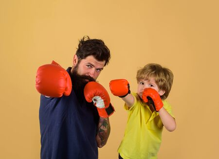 Ready for sparring. Bearded sports man coaching boxing little boy in red boxing gloves. Little boy sportsman at boxing training with coach on boxing ring. Sportswear fashion. Parenthood relationship Stok Fotoğraf