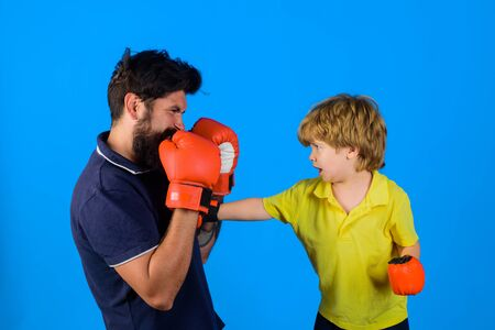 Little kid boxing. Dad and his son in boxing gloves. Child and instructor training in boxing ring. Happy father and son boxing together. Boy play fight with his coach Stok Fotoğraf