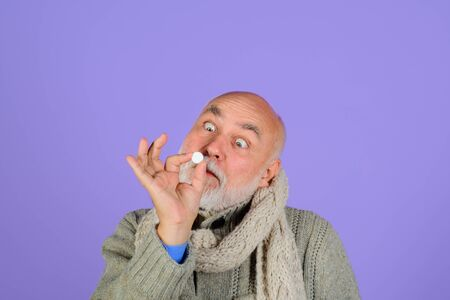Senior man using nasal spray. Bearded man uses spray drops of medicine in his nose. Man spraying drops in his nose. Man with nasal drops. Treatment for allergies or common cold. Rhinitis, allergy Stok Fotoğraf