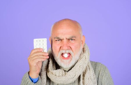 Man taking pills. Man taking pharmaceutical pills. Sore throat. Sick man holds blister pack with tablets. Treatment. Pharmaceutical drug. Medicine and medication. Treat pain, fever and inflammation Stok Fotoğraf