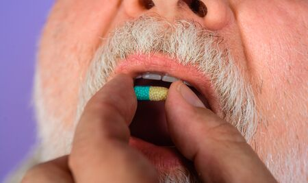 Sick man holds pill. Close up. Treatment. Pharmaceutical drug. Medicine and medication. Treat pain, fever and inflammation. Man taking pills. Man taking pharmaceutical pills
