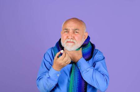 Sore throat. Man wrapped in scarf suffering from sore throat. Treatment pill. Medicine. Senior man taking pharmaceutical pills. Bearded man with sore throat taking pills. Ill man take pill for throat Stok Fotoğraf
