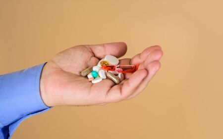 Different pills prescribed by doctor. Medicine pills in hand. Tablets in hand of patient. Medical concept. Hand of man holds different pills. Medicine, treatments and healthcare. Man hands with pills