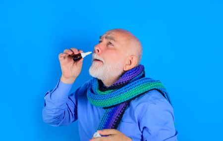 Treatment for allergies or common cold. Rhinitis, allergy. Senior man using nasal spray. Bearded man uses spray drops of medicine in his nose. Man spraying drops in his nose. Man with nasal drops