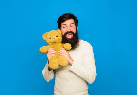 Teddy bear. Smiling man with teddy bear. Bearded man with Teddybear plush toy. Gift and present. Holiday. Celebration. Smiling man hugs teddy bear. Birthday or anniversary. Bearded man with plush toy Stok Fotoğraf