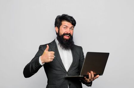 Man with laptop computer shows thumb up. Confident business expert. Business man with PC. Handsome businessman working with notebook. Office, business, technology, internet. Bearded man with laptop Stok Fotoğraf