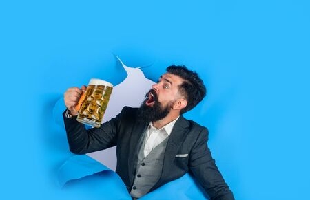 Lager and dark beer. Bearded man holds craft beer looking through paper hole. Drinks, alcohol, leisure, people concept. Stylish man with beard hold mug of beer. Bearded man drinking beer. Oktoberfest