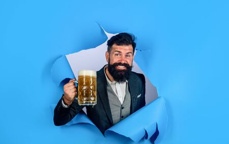 Bearded man drinking beer. Stylish man with beard hold mug of beer. Oktoberfest. Lager and dark beer. Bearded man holds craft beer looking through paper hole. Drinks, alcohol, leisure, people concept Stok Fotoğraf