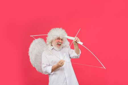 Happy Valentine's Day. February 14. Old Cupid with bow. Valentines day angel. Man in angel costume. Cupid. Amour. God of Love. Concept of Valentines Day Standard-Bild - 137750550