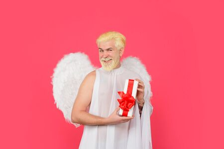 Cupid angel with present box. Valentines day angel. Cupid with gift. Love concept. Cupid. Smiling man in angel costume. February 14. Cupid with gift box. Valentine angel. Happy Valentines Day. Amour