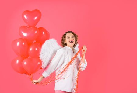 St Valentine day. Love story concept. Female angel. Valentines day. Cupid with heart shaped balloons. Happy woman with angel wings holds heart balloons. Sexy woman dressed as angel with red balloons Standard-Bild - 137750552