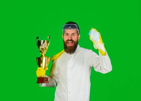 Man from professional cleaning service. Domestic work. Bearded man in uniform and gloves with cleanser spray and gold trophy cup. Cleaning, cleanliness, cleaning products. Housework, housekeeping Stok Fotoğraf