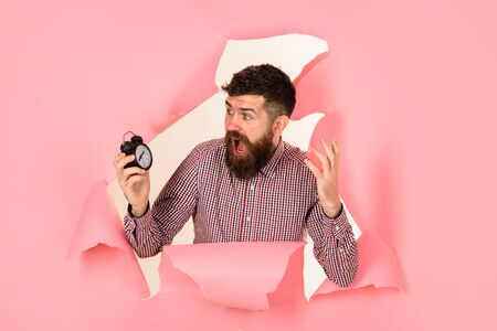 Time for shopping. Surprised bearded man through hole in paper holds alarm clock. Time, deadline. Discount, sale, season sales. Time concept. Shocked bearded man holds clock. Man is late. Losing time Stock Photo