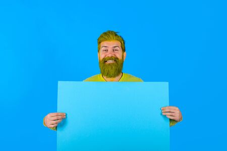 Smiling bearded man holds advertising board. Advertising and sale. Online shopping. Advertising banner. Seasons sale. Discount. Black friday. Marketing. Add. Copy space for text. Sellout