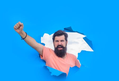 Excited bearded man through hole in blue paper.Through paper. Advertising. Happy. Emotions. Smiling. Discount. Sale. Season sales. Sellout. Man through paper. Victory