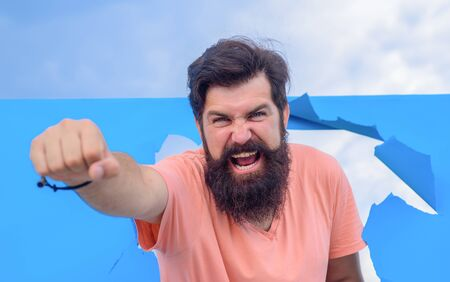Close up portrait of excited bearded man through hole in blue paper. Win. Through paper. Advertising. Happy. Emotions. Smiling. Discount. Sale. Season sales. Man through paper. Victory