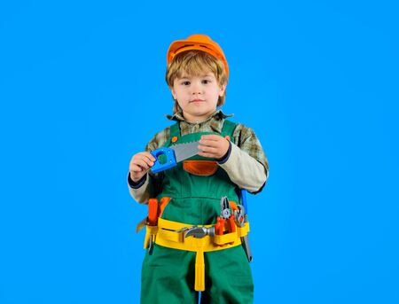 Little boy in builders uniform holds saw. Cute boy plays construction worker. Little boy with helmet and tools. Builder. Kid game. Tools for building. Little repairman. Kid as construction worker Stok Fotoğraf