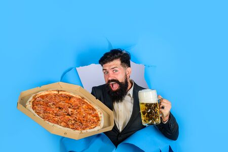 Pizza time. Fastfood. Italian food. Pizza delivery concept. Bearded man with tasty pizza and beer looking through paper hole. Satisfied man with beard and mustache enjoy delicious pizza and cold beer Stok Fotoğraf