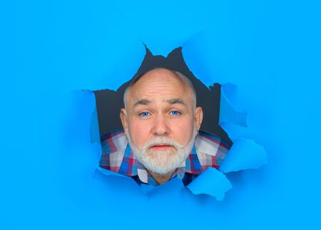 View of male face through hole in blue paper. Crying bearded man through hole in paper. Copy space for advertising. Discount, sale, season sales