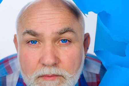 Crying bearded man through hole in blue paper. Copy space for advertising. Discount, sale, season sales. Through paper. Advertising. Close up portrait