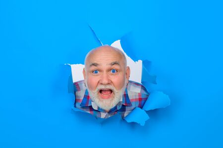 Happy bearded man through hole in blue paper. Discount. Sale. Season sales. Sellout. Through paper. Advertising Stok Fotoğraf
