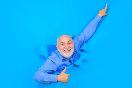 Happy old bearded man through hole in blue paper. Old man points up. Copy space for advertising. Discount, sale, season sales. Through paper. Advertising