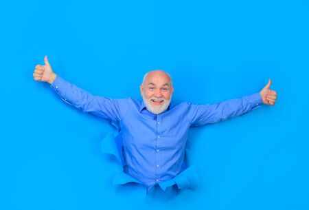 Smiling old bearded man through hole in blue paper. Discount, sale, season sales. Through paper. Advertising. Old man points up. Copy space for advertising