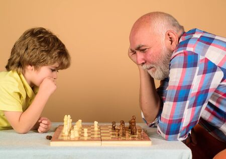Checkmate. Little boy think or plan chess game. Games and activities for children. Grandfather and grandson playing chess. Child boy playing chess with grandfather. Little boy learning to play chess