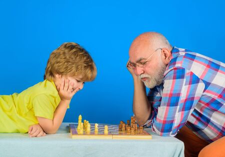 Games and activities for children. Checkmate. Little boy think or plan chess game. Grandfather and grandson playing chess. Child boy playing chess with grandfather. Little boy learning to play chess