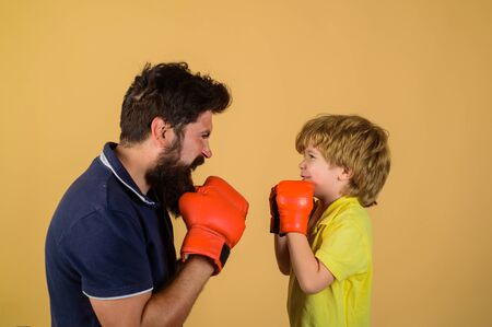 Little kid boxing. Dad and son in boxing gloves. Child and instructor training in boxing ring. Happy father and son boxing together. Boy fight with coach