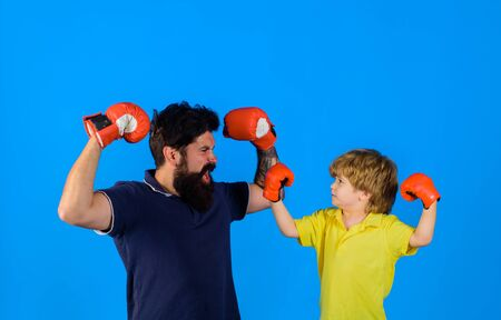 Parenthood relationship. Little boy sportsman at boxing training with coach on boxing ring. Ready for sparring. Bearded sports man coaching boxing little boy in red boxing gloves.Sportswear fashion