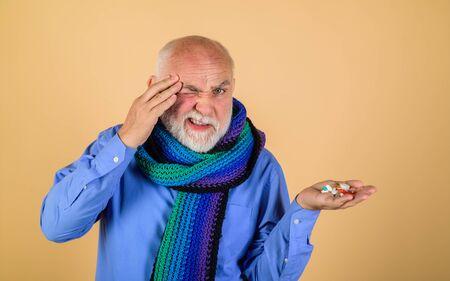 Man taking pills. Migraine. Headache. Sore throat. Treatment. Pharmaceutical drug. Pain. Old man touch forehead. Pharmaceutical pills