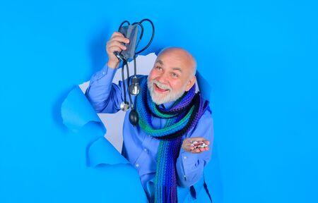 Sphygmomanometer. Old man through hole in paper. Advertising. Health care. Pressure. Medicine. Health Stok Fotoğraf