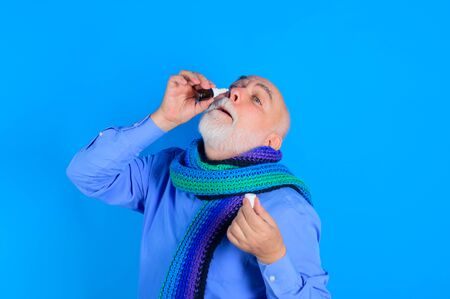 Treatment for allergies or common cold. Senior man using nasal spray. Bearded man uses spray drops of medicine in his nose. Man spraying drops in his nose. Man with nasal drops. Rhinitis, allergy Stok Fotoğraf