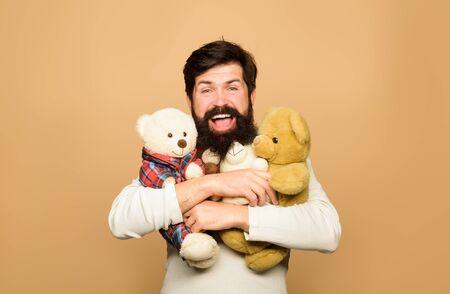 Teddy bear. Man with fluffy teddy bear. Bearded man hugs Teddy bear plush toy. Gift and present. Holiday. Celebration. Smiling man hugs teddy bear. Birthday or anniversary. Bearded man with plush toy
