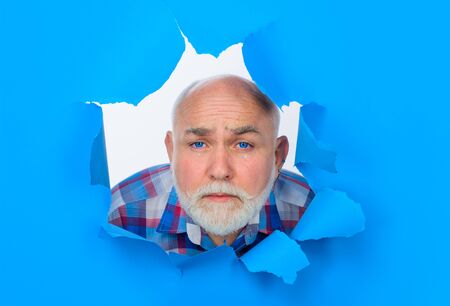 Crying bearded man through hole in blue paper. Sad. Emotions. Cry. Tears. Discount, sale, season sales. Through paper. Advertising