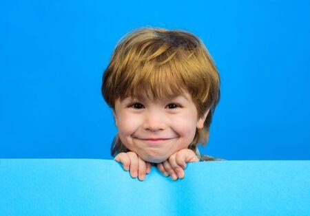 Smiling boy holds blank board. Child boy holds empty billboard. Little boy holds blank advertising banner. Funny little boy with empty board for your text. Blank sign for text. Advertising. Children's goods 版權商用圖片
