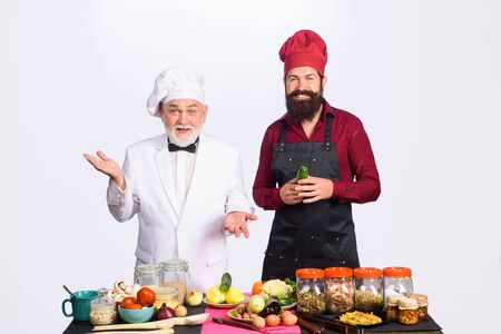Two chefs cooking. Professional culinary. Bearded man in kitchen apron. Bearded man chef in uniform. Cook. Chef. Ready to cook. Healthy lifestyle. Diet. Healthy food. Health care