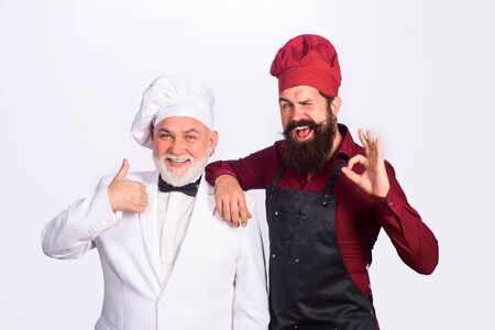Two chefs cooking. Professional culinary. Bearded man in kitchen apron. Bearded man chef in uniform. Cook. Chef. Gesture ok. Thumbs up. Healthy food Foto de archivo