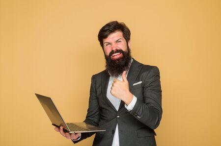 Office, business, technology, internet. Excited man with laptop shows thumbs up. Businessman working with notebook in office. Business man with computer at workplace. Businessman works with laptop