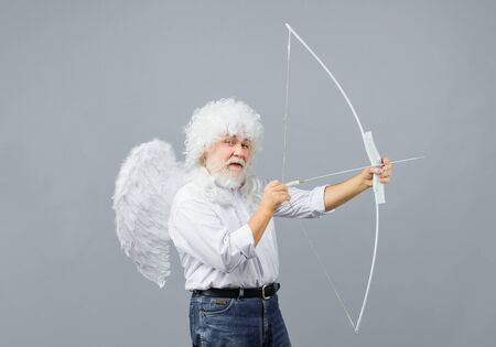 Arrow of love. Cupid throws arrow with bow for valentine day. Male angel with bow and arrow. Cupid angel with bow and arrows. Cupid in valentine day. Valentines Day concept. Valentines day cupid Stock Photo