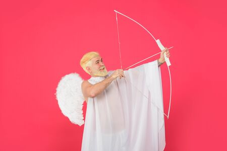 Cupid firing arrow. Postcard for Valentines Day. Male angel Cupid with bow and arrows of love. Saint Valentines Day celebration. Valentines cupid with wings. Cupid Valentine's day with bow and arrow