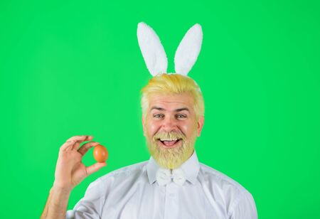 Happy Easter. Happy bearded man with rabbit ears holds Easter egg. Man in bunny ears holds Easter egg. Rabbit man. Easter eggs. Spring time. Eggs hunt. Spring holidays 免版税图像