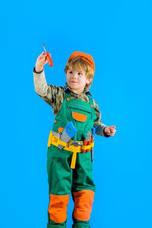 Worker with tools. Repair. Little boy in builder uniform with tools belt. Little kid repairman. Builder boy in helmet and toolbelt. Happy boy with tools for building. Child game Foto de archivo