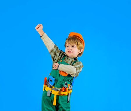 Builder boy. Little boy in builders uniform with toy tools. Kid playing with repair tools. Construction worker. Repair concept. Little boy in helmet and tools. Little repairman. Tools for building Foto de archivo