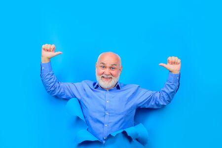 Heureux vieil homme barbu à travers le trou dans du papier bleu. Le vieil homme montre les pouces vers le haut. Espace de copie pour la publicité. Remise, vente, soldes de saison. Par le papier. Publicité.