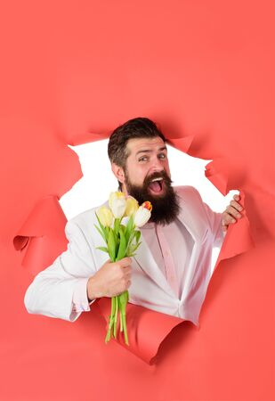Bouquet of tulips. Womens Day. Businessman with bouquet of tulips looking through paper. Bearded man holds bouquet of flowers. Businessman with bouquet tulips for birthday. Smiling man holds flowers