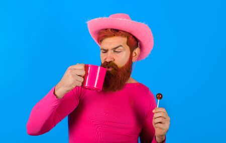Cowboy with cup. Portrait of cowboy. Lollipop. Cowboy drinking. American bandit. American West. Western man with hat. Pink velvet cowboy hat. Gay Stockfoto